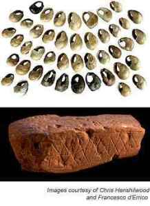 Pierced, dyed beads and incised block of red ochre from Blombos Cave, South Africa
